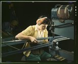 A girl riveting machine operator at the Douglas Aircraft Company plant joins  Stock Photos