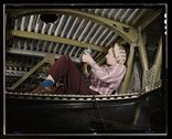 An A-20 bomber being riveted by a woman worker at the Douglas Aircraft Compan Stock Photos
