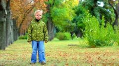 Cute 4 year old little boy jumping in park. beautiful child. happy people Stock Footage