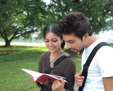Young indian / asian college students reading a book outside the campus. Stock Photos