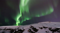 Brilliant northern lights aurora over snowy rock ledge, Iceland 4k Stock Footage