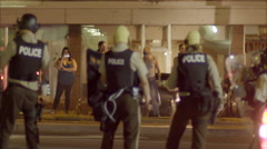 Police with automatic weapons patrol the streets during the Ferguson riots. Stock Footage