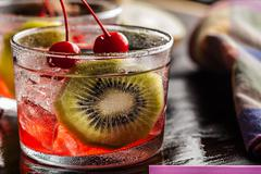 cold summer cocktail drink with cherry and kiwi - stock photo