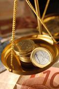Euro coins in pan of weighing balance Stock Photos