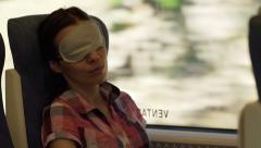 Young woman sleeping with eye band mask on a train  HD Stock Footage