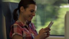Happy woman texting on smartphone during train travel HD Stock Footage