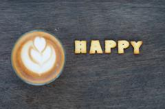"""A cup of latte art and alphabet """"happy """" made from bread cookies Stock Photos"""