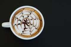 a cup of latte art on black background - stock photo