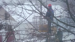 Work of municipal service - cut away branches during a snow storm Stock Footage