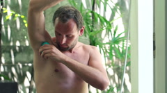 Man applying antiperspirant after shower on his armpit in the bathroom HD Stock Footage