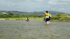 People crossing a river walking into the water Stock Footage