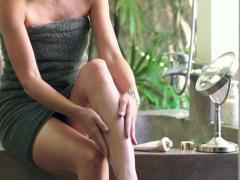Pretty woman applying lotion moisturizer on her leg in bathroom NTSC Stock Footage