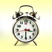 Vintage alarm clock, isolated on the yellow background, clipping path included. - stock photo