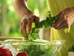 Woman hands tearing salad leaves into bowl, slow motion shot at 120fps NTSC Stock Footage