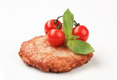 fried hamburger patty and red cherry tomatoes - stock photo