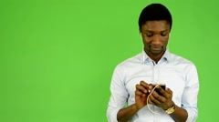 Young handsome black man listens music with earphone(smartphone) - green screen Stock Footage