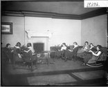 Women students seated around Bishop Hall fireplace 1919 Stock Photos