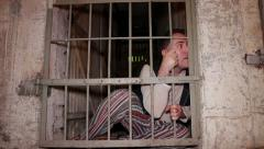 Mad prisoner looks through the bars Stock Footage