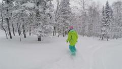 Snowboarder girl rides in powder snow - stock footage