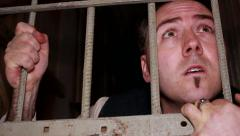 Slide shot of frightened man behind bars Stock Footage