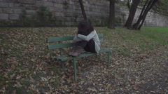 Woman sitting alone on the bench, steadycam shot, slow motion shot at 240fps Stock Footage