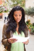 african american woman reading a letter - stock photo