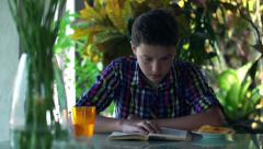 Teenager reading book by the table at home HD Stock Footage
