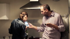 Happy couple talking and looking at smartphone while cooking in kitchen  HD Stock Footage