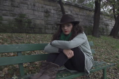 Lonely woman sitting on the bench, steadycam shot, slow motion shot at 240fps Stock Footage
