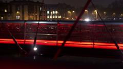 View of city and pedestrian walking on footbridge at night, steadycam shot Stock Footage