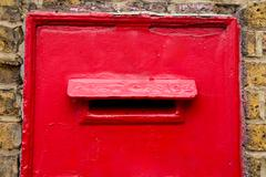 A traditional red post box in a wall. Kuvituskuvat