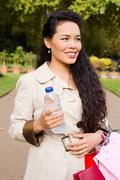 woman holding water bottle and bags. - stock photo
