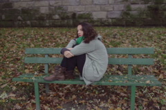 Unhappy woman sitting on the bench, steadycam shot, slow motion shot at 240fps Stock Footage