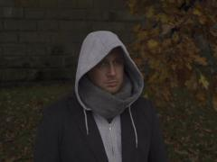 Man with hoodie standing on boulevard, steadycam shot, slow motion shot Stock Footage