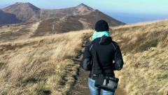 Woman walking alone on footway in the mountains, steadycam shot Stock Footage