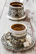 traditional turkish coffee in traditional silver cup with silver pot.... - stock photo