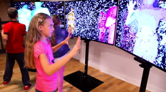 Childrens playing in front of the holographic screen - stock footage