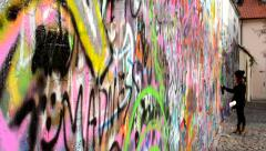 Lennon Wall with people - woman sprayed Stock Footage