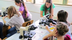Teachers educate children how to use a microscope Stock Footage