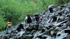 Hikers walk on the large rocks during heavy rains slow motion Stock Footage