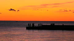 Fishermans on the sea catching fish from pier at sunset Stock Footage