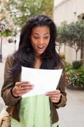 african american woman reading document looking surprised. - stock photo