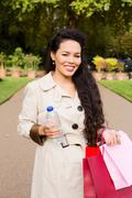 woman holding a water bottle and bags. - stock photo