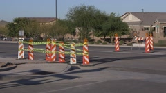 Road construction pylons with caution tape, cars pass by Stock Footage