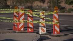 Road construction pylons with caution tape, cars pass by 03 Stock Footage