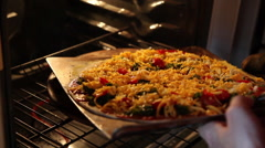 Placing a homemade pizza into an oven Stock Footage