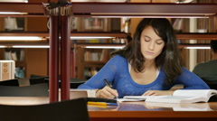 Young woman studies at the library Stock Footage