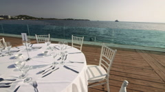 Stock Video Footage of Luxurious formal dinner table outdoors at sunset with sea view