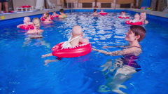 Mothers swimming in a circle on a lesson with small children - stock footage