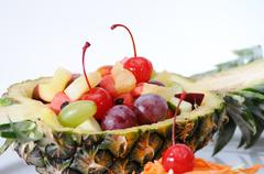 Fruits salad in pineapple on white plate, food stylist Stock Photos